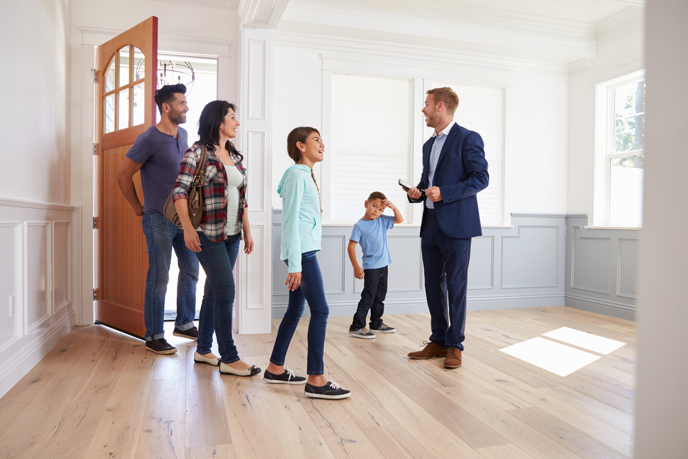 A young family being shown a house by a realtor