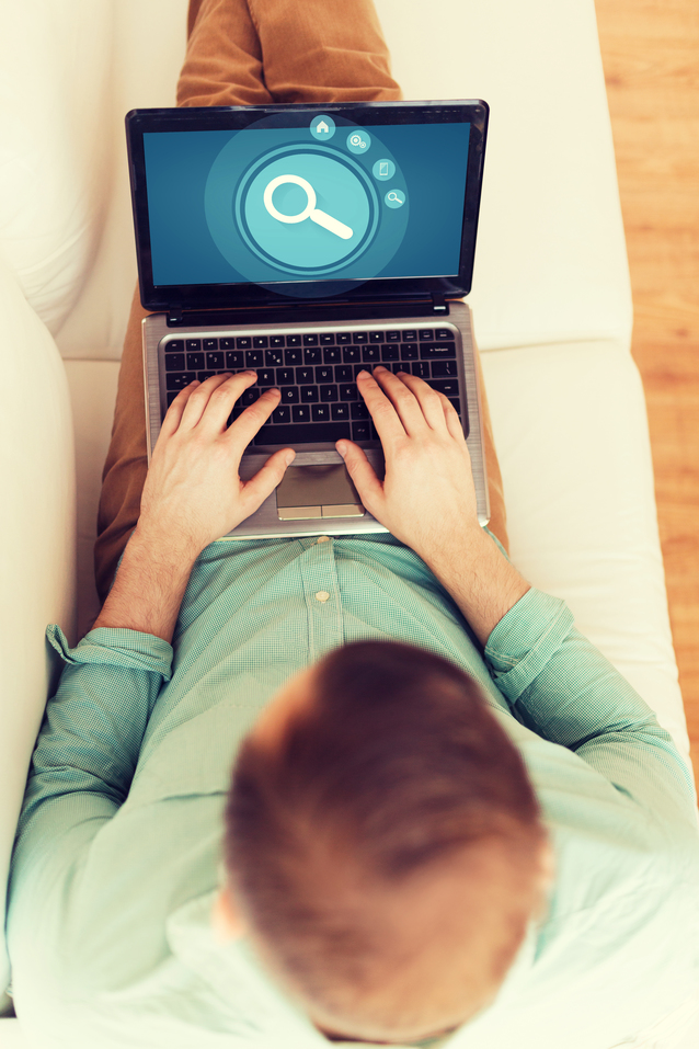 technology, leisure, advertisement and lifestyle concept - close up of man working with laptop computer displaying magnifying glass icon on screen and sitting on sofa at home