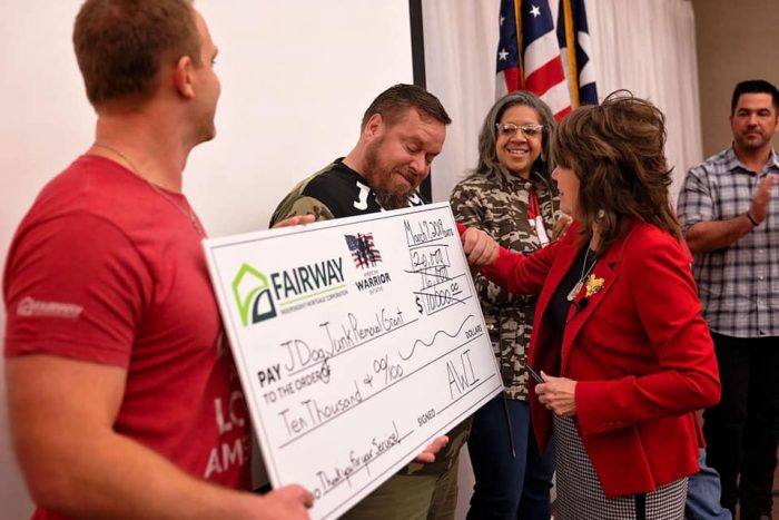 Fairway employees honoring a Veteran with a large check
